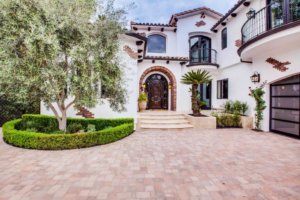 white stucco home with beautiful arches highlight this spanish design style home