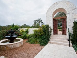 spanish courtyard with water fountain and walkway leading to spanish arch and doorway