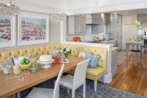 bright white kitchen and dining room with wood flooring with yellow seating area