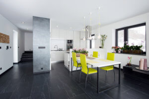 white kitchen cabinets against a dark floor with industrial style kitchen table