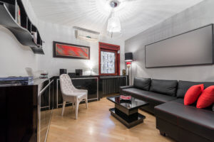 black couches and cabinets with pops of red in living area