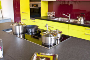 post modern style kitchen with bright yello cabinets and red backsplash